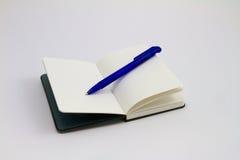 Czarny notatnik z błękitnym piórem Fotografia Stock