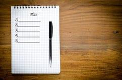 Czarny notatnik z piórem na drewnianym tle Obrazy Stock
