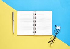 Czarny notatnika puste miejsce, parawanowy pióro umieszczający na pastelowym tle i koloru żółtego i błękita Stosowny dla grafika  Obrazy Royalty Free
