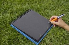 czarny notes trawy. Zdjęcia Royalty Free