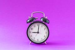 Czarny nowożytny budzik ustawiający przy dziewięć o ` zegarem, odosobnionym, pracy szkoła zaczyna pojęcie, pozafioletowy tło obraz royalty free