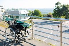 Czarny nowy wózek inwalidzki opuszczać na tarasie Obrazy Royalty Free