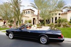 Czarny odwracalny samochód parkujący w frontowym f luksusu domu Fotografia Stock