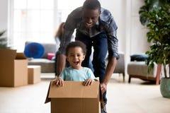 Czarny ojciec i syn bawić się z pudełkiem w domu zdjęcie stock