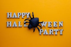 Czarny pająk zamiast listu O na eleganckim wpisowym SZCZĘŚLIWYM HALLOWEEN przyjęciu Słowa od drewnianych listów na jaskrawej poma zdjęcia royalty free