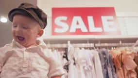 Czarny Piątek jest szczęśliwy z dużymi rabatami w modnym sklepie, szczęśliwy roześmiany niemowlak w elegancką nakrętkę zbiory