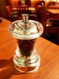 Czarny pieprz w projektującej szklanej butelce na stole Boczny widok Obrazy Stock
