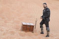 Czarny pirat w pustyni z skarbu pudełkiem Obraz Royalty Free
