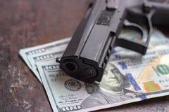 Czarny pistolet na Ameryka?skim dolara tle Militarny przemys?, wojna, globalny handel broni?, broni sprzeda?, kontraktacyjny zabi obrazy stock