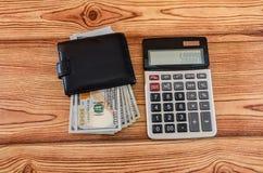 Czarny portfel z dolarami i kalkulator na drewnianym tle fotografia royalty free