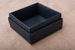 Czarny prezenta pudełko na brown tle Obraz Stock