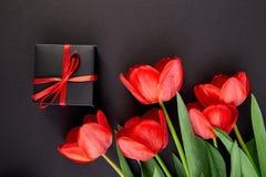 Czarny prezenta pudełko z czerwonym tasiemkowym pobliskim czerwonym tulipanem Zdjęcia Stock