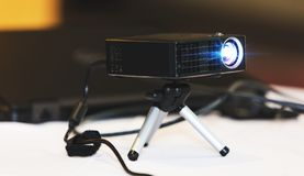 Czarny projektor z tripod instalującym na bielu stole w sala, lub fotografia stock