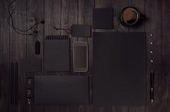 Czarny pusty materiały ustawiający z telefonem, słuchawka, kawa na ciemnym drewnianym tle Obrazy Stock