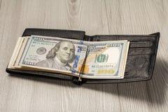 Czarny rzemienny portfel z dolarowymi rachunkami na popielatym drewnianym backgrou Fotografia Stock