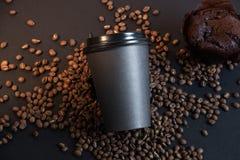 Czarny słodka bułeczka w kawowych fasolach na czarnym tle i filiżanka zdjęcie royalty free