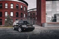Czarny samochodowy Subaru Forester parkował blisko nowożytnych czerwonych budynków w Moskwa przy dniem Obrazy Stock