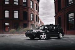 Czarny samochodowy Subaru Forester parkował blisko nowożytnych czerwonych budynków w Moskwa przy dniem Zdjęcie Royalty Free
