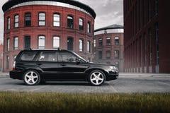 Czarny samochodowy Subaru Forester parkował blisko nowożytnych czerwonych budynków w Moskwa przy dniem Zdjęcia Royalty Free