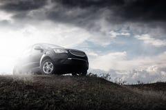 Czarny samochodu pobyt na wzgórzu w dramatycznych chmurach przy dniem obraz royalty free