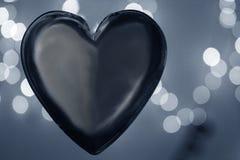 Czarny serce nad zamazanym bokeh skutka tłem Obrazy Stock
