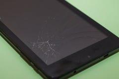 Czarny smartphone z łamanym pokazem na jasnozielonym backgrou Zdjęcie Stock