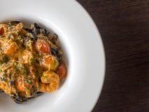 Czarny spaghetti w pomidorowym kumberlandzie z garnelą, pomidor kropi z pikantność i serem na bielu talerzu Świeży i czysty naczy Fotografia Royalty Free