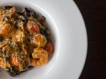 Czarny spaghetti w pomidorowym kumberlandzie z garnelą, pomidor kropi z pikantność i serem na bielu talerzu Świezi i czyści naczy Zdjęcie Stock