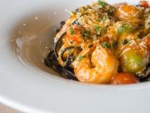 Czarny spaghetti w pomidorowym kumberlandzie z garnelą, pomidor kropi z pikantność i serem na bielu talerzu Świezi i czyści naczy Obraz Royalty Free