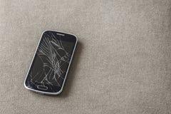 Czarny stary telefon kom?rkowy z krakingowym ekranem na lekkim p??tno kopii przestrzeni tle Gad?etu utrzymania i naprawy poj?cie obrazy stock