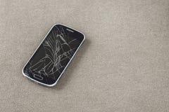 Czarny stary telefon kom?rkowy z krakingowym ekranem na lekkim p??tno kopii przestrzeni tle Gad?etu utrzymania i naprawy poj?cie zdjęcia stock