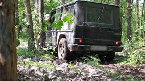Czarny SUV dostać zablokowanym w błocie w lesie, droga zdjęcie wideo
