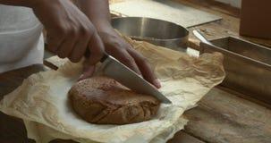 Czarny szef kuchni bierze out tort i ciie je w połówce zdjęcie wideo