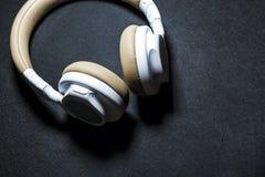 Czarny tło Duże słuchawki dla słuchać muzyka Biel i beżowy kolor skóra nowożytne technologie Przenośny wyposażenie fotografia royalty free