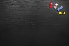 Czarny tło z kolorowymi zabawkarskimi samochodami Zdjęcia Stock