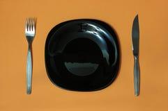 Czarny talerz, rozwidlenie, nóż Obrazy Stock