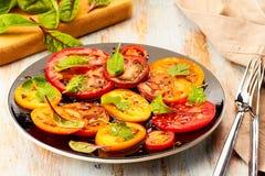 Czarny talerz sałatka z pokrojonymi pomidorami słuzyć na drewnianym stole Zdjęcia Royalty Free