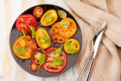 Czarny talerz sałatka z pokrojonymi pomidorami słuzyć na drewnianym stole Obraz Royalty Free