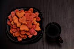 Czarny talerz z czerwonymi sercowatymi ciastkami i kubkiem herbata na czarnym stole, walentynka dzień Odgórny widok Obraz Stock