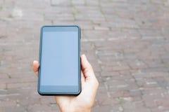 Czarny telefon komórkowy w kobiety ręce tło miejskie Fotografia Royalty Free