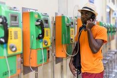 Czarny turystyczny mężczyzna opowiada na payphone podczas gdy myśleć fotografia royalty free