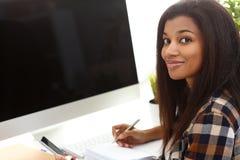 Czarny uśmiechnięty kobiety obsiadanie przy miejsce pracy pisze coś obrazy royalty free