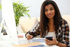 Czarny uśmiechnięty kobiety obsiadanie przy miejsce pracy pisze coś zdjęcie royalty free