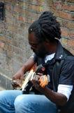 Czarny uliczny muzyk siedzi przeciw ścian sztuk gitarze Londyn Anglia Obraz Royalty Free