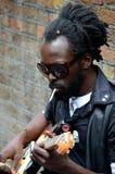 Czarny uliczny muzyk siedzi przeciw ścian sztuk gitarze Londyn Anglia Zdjęcia Stock