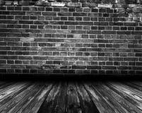 Czarny wewnętrzny pokój z ściana z cegieł i drewnianą podłoga zdjęcia stock