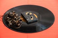 Czarny winylowy rejestr na barwionym tle i cassetta Fotografia Royalty Free