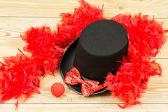 Czarny wysoki kapelusz, czerwony puszysty piórkowy boa, czerwony łęku krawat i czerwieni clow, Zdjęcia Stock