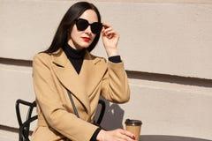 Czarny z włosami Europejski magnesowy żeński mienia brązu papercup w jeden ręce, dotykający czarnych okulary przeciwsłonec zdjęcie stock