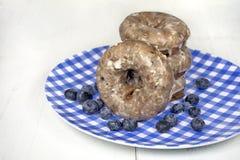 Czarnych jagod donuts na w kratkę talerzu Fotografia Stock